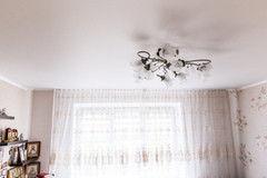 Натяжной потолок ТЕХО белый сатиновый в спальне с люстрой